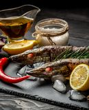 Pike royally. Raw fresh river fish on plate cutting board an old wooden background. Russian cuisine. fish with spices for cooking. Top view stock images