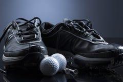 Piłki golfowe, trójniki i buty na zmroku, - błękitny tło Zdjęcie Stock