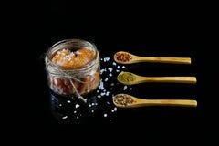 Pikkaviar, fiskrom i en glass krus, träskedar med kryddor för fisken, hav som är salt på en svart bakgrund, närbild, uppsättning Royaltyfri Fotografi