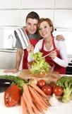 Piękna Amerykańska para pracuje w domu kuchnię w fartuchu miesza jarzynowy sałatkowy ono uśmiecha się szczęśliwy Zdjęcie Royalty Free