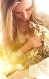 Piękna brunetki dziewczyna i jej imbirowy kot Zdjęcia Royalty Free