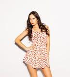 Piękna brunetki dziewczyna z długie włosy i niebieskie oczy pozuje w jaskrawej lato skrótu sukni na białym tle salowy Fotografia Royalty Free