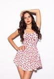 Piękna brunetki dziewczyna z długie włosy i niebieskie oczy pozuje w jaskrawym lato skrótu sukni nex biały tło salowy Obraz Royalty Free