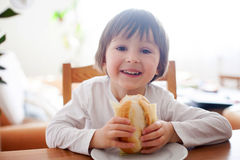 Piękna chłopiec, je kanapkę w domu, warzywa na Obrazy Stock