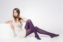 Piękna kobieta jest ubranym pończochy pozuje w studiu z długimi seksownymi nogami - folujący ciało Zdjęcia Stock