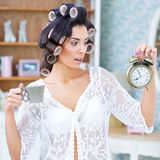 Piękna kobieta patrzeje zaskakujący przy zegarem w włosianych curlers Zdjęcia Stock