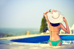 Piękna kobieta sunbathing na krawędzi basenu Zdjęcia Royalty Free
