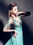 Piękna kobieta w zieleni smokingowy pozować dramatyczny indoors Obrazy Stock