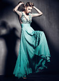Piękna kobieta w zieleni smokingowy pozować dramatyczny indoors Obraz Stock