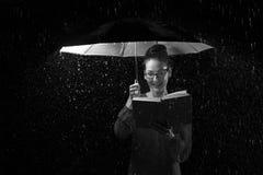 Piękna kobieta z smokingowym czytaniem książka w deszczu pod umbre Zdjęcia Royalty Free