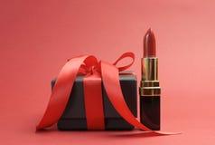 Piękna luksusowa czerwona pomadka z czarnego pudełka prezentem - horyzontalnym. Obraz Stock