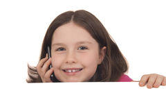 Piękna mała dziewczynka opowiada na telefon komórkowy za odbitkowym spac Fotografia Stock