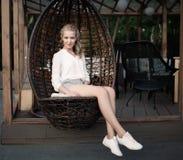 Piękna młoda blond dziewczyna siedzi w łozinowym krześle przy plenerową kawiarnią na wieczór, ono uśmiecha się i spojrzeniu z dłu Obraz Stock