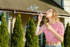 Piękna młoda blondynki dziewczyna dmucha mydlanych bąble Fotografia Royalty Free