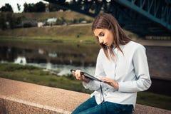 Piękna młoda dziewczyna używa cyfrową pastylkę Zdjęcia Stock