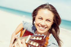 Piękna młoda kobieta bawić się gitarę na plaży Zdjęcia Royalty Free