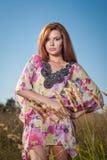 Piękna młoda kobieta w dzikich kwiatów polu na niebieskiego nieba tle Portret atrakcyjna czerwona włosiana dziewczyna z długie wł Obrazy Royalty Free
