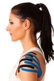 Piękna młoda kobieta z kinesiotape na jej ramieniu mobili Zdjęcia Royalty Free