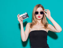 Piękna modna dziewczyna pozuje rocznik kamerę w i trzyma czerń okularach przeciwsłonecznych na zielonym tle w studiu i sukni Obrazy Stock