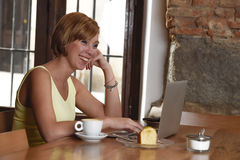 Piękna pomyślna kobieta pracuje przy sklep z kawą z laptopem cieszy się filiżankę Obrazy Royalty Free
