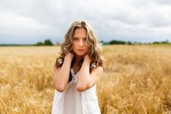 piękna śródpolna dziewczyna patrzeje uśmiechy w górę pszenicznych potomstw Zdjęcia Stock