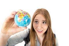 Piękna studencka dziewczyna trzyma małą światową kulę ziemską w jej ręce wybiera wakacje miejsce przeznaczenia w podróży turystyk Fotografia Stock