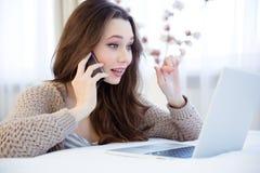 Piękna zadziwiająca kobieta opowiada na telefonie komórkowym i używa laptop Fotografia Royalty Free