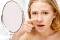 Piękna zdrowa kobieta przestrasząca zobaczył w lustrzanych zmarszczeniach i trądziku Zdjęcia Royalty Free