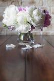 Piękne peoni róże w wazie na drewnianym tle Fotografia Stock