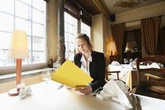 Pięknego klienta czytelniczy menu przy restauracja stołem Fotografia Royalty Free