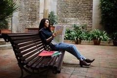 Pięknej dziewczyny pojawienia Azjatycki obsiadanie na ławce w malowniczej ulicy i spojrzeń mapie Fotografia Stock