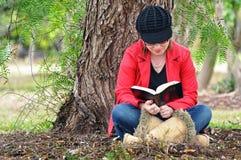 Pięknej młodej kobiety czytelnicza biblia pod dużym drzewem Obraz Stock
