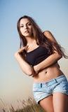 Piękni młoda dziewczyna stojaki w polu przy zmierzchu czasem Fotografia Royalty Free