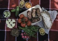 piknik Czerwona szkocka krata świezi warzywa, chleb na którym kłama pyknicznego jedzenie, grill, kiełbasy na ogieniu Skład, śwież obrazy royalty free