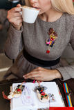 Piękny blondynki dziewczyny obsiadanie przy kawiarnią z filiżanką kawy i tortem pracuje i remisy kreślą w notatniku Zdjęcia Stock