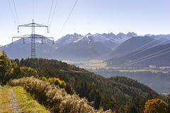 Pilão da eletricidade que cruza os cumes no Tirol Fotografia de Stock