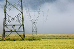 Pilão de alta tensão da eletricidade grande com linhas elétricas Imagem de Stock