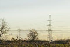 Pilón de alto voltaje con los cables y paisaje Foto de archivo