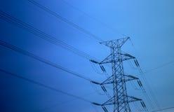 Pilón de la electricidad contra el cielo azul y la puesta del sol de la oscuridad Imagenes de archivo