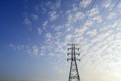 Pilón de la electricidad contra el cielo azul y la puesta del sol de la oscuridad Imagen de archivo