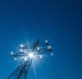Pilón de la electricidad contra la luz Foto de archivo libre de regalías