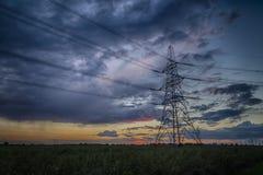 Pilón de la electricidad en la oscuridad y tormenta en el horizonte Foto de archivo
