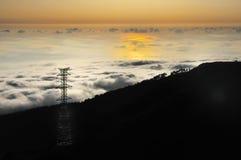 Pilón de la electricidad sobre el valle en la puesta del sol, Lomba das Imagenes de archivo