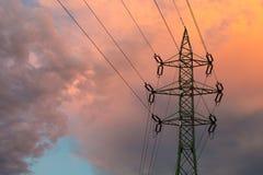Pilón de la electricidad y nubes anaranjadas Imagen de archivo