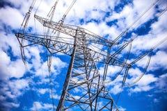Pilón de la transmisión de la electricidad contra el cielo azul en la oscuridad Imagenes de archivo