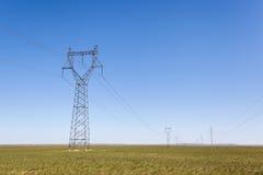 Pilón de la transmisión de la electricidad en pradera imagen de archivo