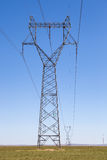 Pilón de la transmisión de la electricidad en pradera fotografía de archivo