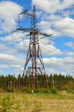 Pilón eléctrico de la transmisión en el campo Fotografía de archivo