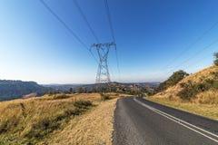 Pilón y líneas eléctricas de arriba al lado de Asphalt Road Imágenes de archivo libres de regalías