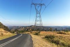 Pilón y líneas eléctricas de arriba al lado de Asphalt Road Fotografía de archivo